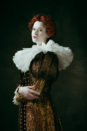 Lovely portrait. Medieval redhead young woman in golden vintage clothing as a duchess standing crossing hands on dark green background. Concept of comparison of eras, modernity and renaissance. Фото со стока