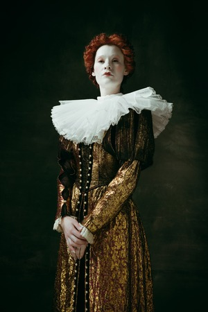 Attention and serious. Medieval redhead young woman in golden vintage clothing as a duchess standing crossing hands on dark green background. Concept of comparison of eras, modernity and renaissance. Фото со стока