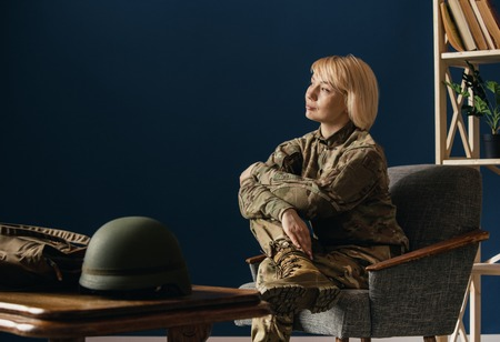 Close up portrait of female soldier. Woman in military uniform waiting for coming home. In doctors consultation, depressed and having problems with mental health and emotions, PTSD, rehabilitation.