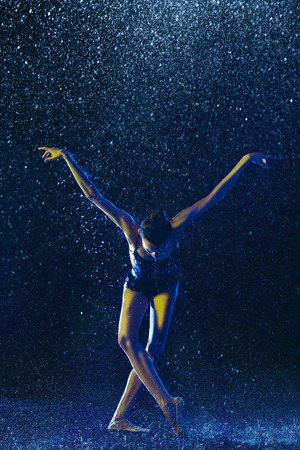 Young female ballet dancer performing under water drops and spray. Caucasian model dancing in neon lights. Attractive woman. Ballet and contemporary choreography concept. Creative art photo.