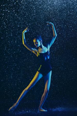 Jeune danseuse de ballet se produisant sous des gouttes d'eau et des embruns. Modèle caucasien dansant dans les néons. Femme captivante. Concept de ballet et de chorégraphie contemporaine. Photo d'art créatif. Banque d'images