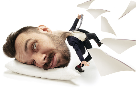 Break night dreams as a glasses. Big head on small body lying on the pillow. Man in black suit cannot wake up cause headache and overslept. Concept of business, working, hurrying up, time limits. Stock Photo