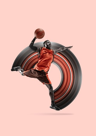 Full length portrait of a basketball player with a ball isolated on coral studio background. Fit african american athlete. Motion, activity, movement, advertising concept. Abstract design.