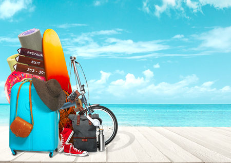 Collage of luggage for travel in front of ocean view. Concept of summertime, resort, journey, trip, travel. Needed things. Serfing board, hat, bicycle, sports mats, camera rubber ring