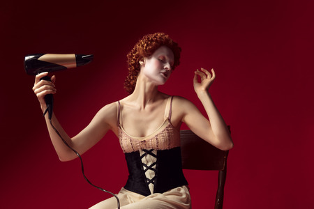 Medieval redhead young woman as a duchess in black corset and night clothes sitting on the chair on red Фото со стока - 122341846