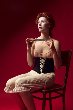 Medieval redhead young woman as a duchess in black corset and night clothes sitting on the chair on red Фото со стока - 122341847
