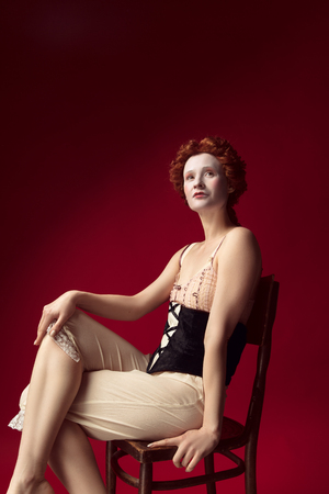 Medieval redhead young woman as a duchess in black corset and night clothes sitting on the chair on red Фото со стока - 122341853