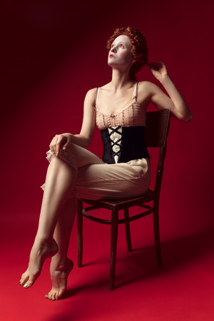Medieval redhead young woman as a duchess in black corset and night clothes sitting on the chair on red Фото со стока - 122341855
