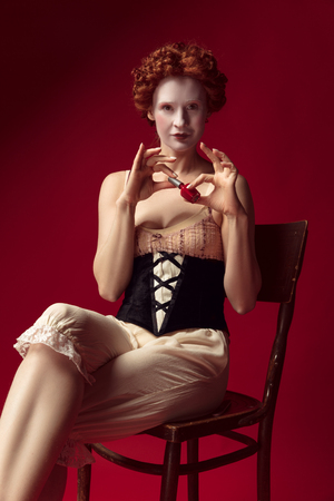Medieval redhead young woman as a duchess in black corset and night clothes sitting on the chair on red