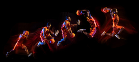 African-american young basketball player of red team in action and neon lights over dark studio