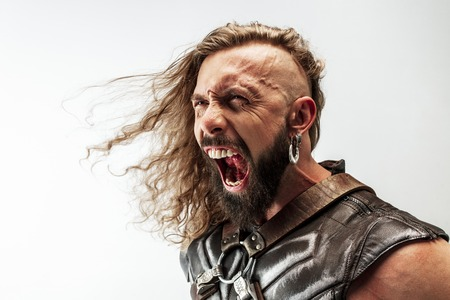 Screaming out. Blonde long hair and muscular male model in leather vikings costume Stock Photo