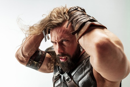 Angry and emotional. Blonde long hair and muscular male model in leather vikings costume