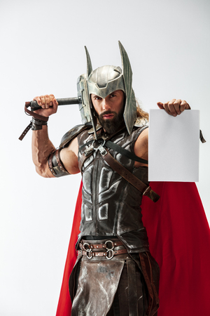 God of thunder. Blonde long hair and muscular male model in leather vikings costume