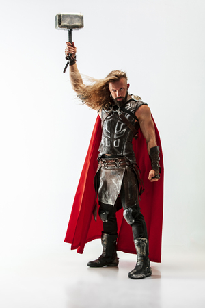 Long hair and muscular male model in leather vikings costume