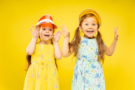 Beautiful emotional little girls isolated on yellow background. Half-lenght portrait of two sisters full of happieness wearing a dresses and caps. Concept of summer, human emotions, childhood. Stock Photo