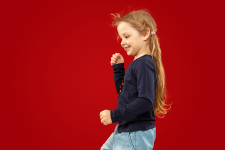 Beautiful emotional little girl isolated on red studio background. Half-lenght portrait of happy child smiling and dancing. Concept of facial expression, human emotions, childhood. Stock Photo - 122162158