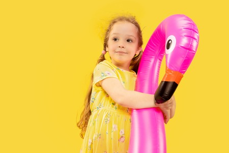Beautiful emotional little girl isolated on yellow background. Half-lenght portrait of happy child wearing a dress and holding rubber pink flamingo. Concept of summer, human emotions, childhood. Stock Photo