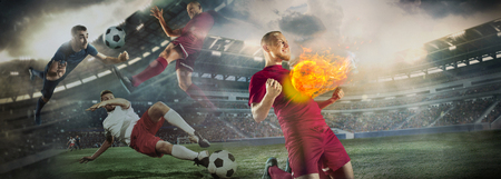 Close up soccer ball in fire on dark background in front of football players of red and blue team fighting for the goal. Creative collage. Movement, action, moving, sport and healthy lifestyle. Stock Photo