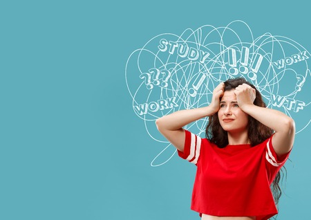 Young caucasian woman with mixed thoughts against blue studio background. Negative space. Concept of thinking confusion, stress out, misunderstanding, facial expression, human emotions.