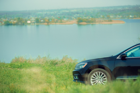 View of modern black car on the rivers side in sunny day. Preparing for weekend trip or journey. Concept of summertime, resort, chilling. Stock Photo