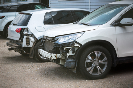 Broken and crashed modern cars after an accident on street, damaged automobile after collision at the city road. Needed tow truck for going to repairs service. Stock Photo