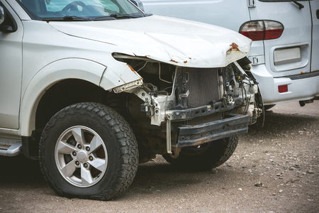 Broken and crashed modern white car after an accident on street, damaged automobile after collision at the city road. Needed tow truck for going to repairs service. Stock Photo