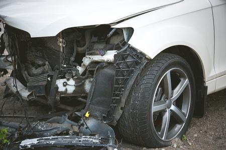 Coche blanco moderno roto y estrellado después de un accidente en la calle, automóvil dañado después de una colisión en la carretera de la ciudad. Grúa necesaria para acudir al servicio de reparaciones.