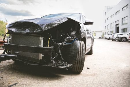 Broken and crashed modern black car after an accident on street, damaged automobile after collision at the city road. Needed tow truck for going to repairs service. Stock Photo
