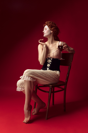Medieval redhead young woman as a duchess in black corset and night clothes sitting on a chair on red background with a glass of wine. Concept of comparison of eras, modernity and renaissance. Stock Photo