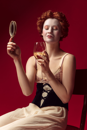 Medieval redhead young woman as a duchess in black corset and night clothes sitting on red background with a mirror and a glass of wine. Concept of comparison of eras, modernity and renaissance. Archivio Fotografico - 122402776