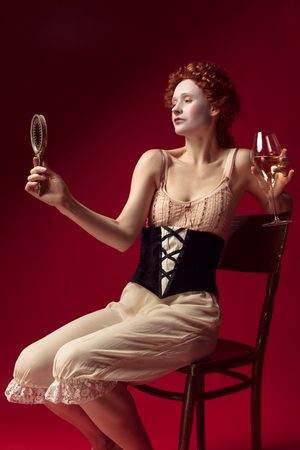 Medieval redhead young woman as a duchess in black corset and night clothes sitting on red background with a mirror and a glass of wine. Concept of comparison of eras, modernity and renaissance.