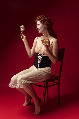 Medieval redhead young woman as a duchess in black corset and night clothes sitting on red background with a mirror and a glass of wine. Concept of comparison of eras, modernity and renaissance. Archivio Fotografico - 122403013