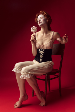Medieval redhead young woman as a duchess in black corset, sunglasses and night clothes sitting on a chair on red background with a candy. Concept of comparison of eras, modernity and renaissance.