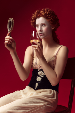 Medieval redhead young woman as a duchess in black corset and night clothes sitting on red background with a mirror and a glass of wine. Concept of comparison of eras, modernity and renaissance. Archivio Fotografico - 122403017