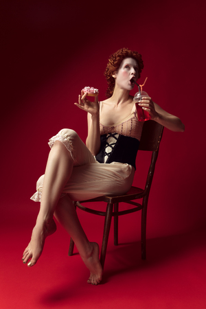 Medieval redhead young woman as a duchess in black corset and night clothes sitting on a chair on red background with a drink and donut. Concept of comparison of eras, modernity and renaissance. Фото со стока - 122403021