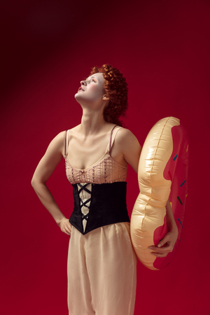 Medieval redhead young woman as a duchess in black corset and night clothes standing on red background with a swim circle as a donut. Concept of comparison of eras, modernity and renaissance.