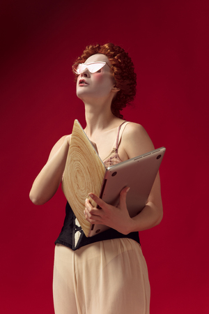 Medieval redhead young woman as a duchess in black corset, sunglasses and night clothes standing on red background with a laptop as a book. Concept of comparison of eras, modernity and renaissance.