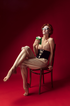 Medieval redhead young woman as a duchess in black corset, sunglasses and night clothes sitting on red background eating fried potato. Concept of comparison of eras, modernity and renaissance. Фото со стока - 122403031