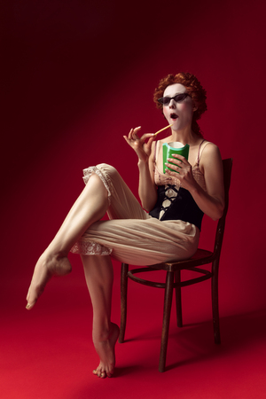 Medieval redhead young woman as a duchess in black corset, sunglasses and night clothes sitting on red background eating fried potato. Concept of comparison of eras, modernity and renaissance.