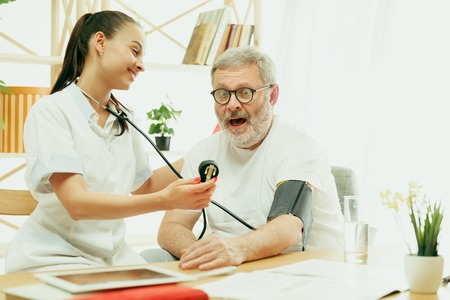 The visiting nurse or health visitor taking care of senior man. Lifestyle portrait at home. Medicine, healthcare and prevention. Girl checking or measuring patients blood pressure during the visit.