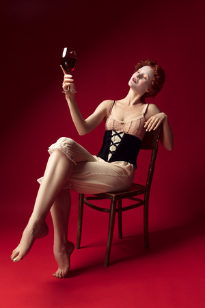 Medieval redhead young woman as a duchess in black corset and night clothes sitting on a chair on red background with a glass of wine. Concept of comparison of eras, modernity and renaissance. Фото со стока