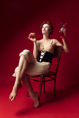 Medieval redhead young woman as a duchess in black corset and night clothes sitting on a chair on red background with a drink and donut. Concept of comparison of eras, modernity and renaissance.