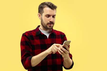 Half-length close up portrait of young man in shirt on yellow background. The human emotions, facial expression concept. Front view. Trendy colors. Negative space. Dialing a number.