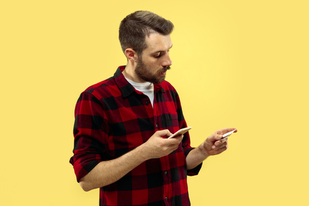 Half-length close up portrait of young man in shirt on yellow background. The human emotions, facial expression concept. Front view. Trendy colors. Negative space. Paying by phone with card. Reklamní fotografie