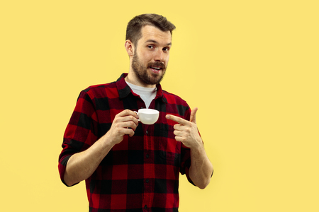 Half-length close up portrait of young man in shirt on yellow background. The human emotions, facial expression concept. Front view. Trendy colors. Negative space. Standing with a cup.