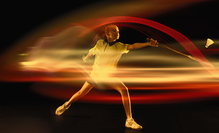 Young girl playing badminton over dark studio background. Female athlete in action with neon light. Concept of motion or movement, sport, healthy lifestyle. Attack and defense. Creative collage. Stock Photo