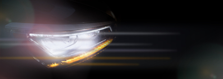 Headlight of a modern car in dense fog against dark background. Exterior details and beauty of technical innovations. Negative space to insert your text or image. Flyer for ad.
