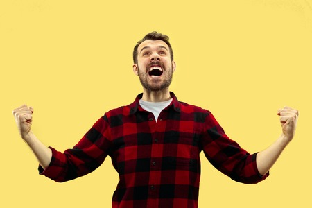 Half-length close up portrait of young man in shirt on yellow background. The human emotions, facial expression concept. Front view. Trendy colors. Negative space. Celebrating as a winner or champion. Stock Photo