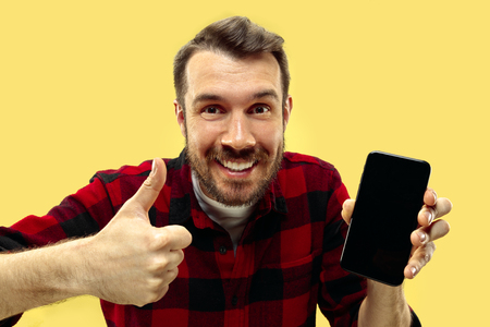 Half-length close up portrait of young man in shirt on yellow background. The human emotions, facial expression concept. Trendy colors. Negative space. Showing a smartphone and a sign of OK.