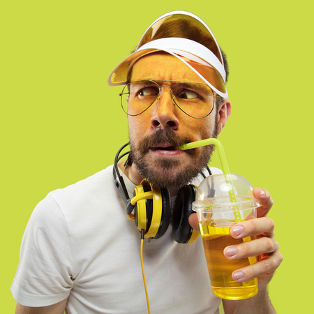 Half-length close up portrait of young man in shirt on yellow background. Male model with headphones and drink. The human emotions, facial expression, summer, weekend concept. Asking and looking.